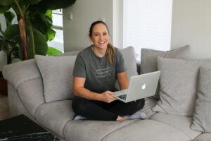 Alexandra Lederer auf einer Couch mit Laptop